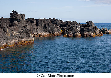 view in ocean and black stones in Azores