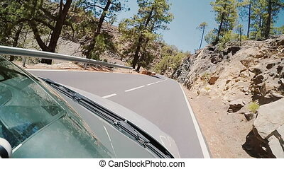 View inside the car to rocky road. Car goes on the serpentine. Footage from two frames.
