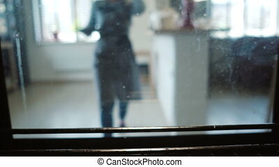 View inside the oven. Young woman open the oven and puts on the baking dish with dough, cooking the cupcakes.