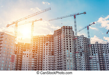 View large-scale construction of a residential complex with a view of construction cranes.