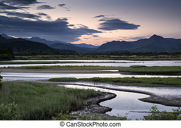 View looking towards Snowdonia mountain range landscape during a summer sunset