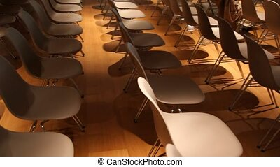 View moves from empty brown chairs to one with newspaper on top in some conference hall