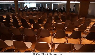 View moves from many to one chair in some dark conference hall