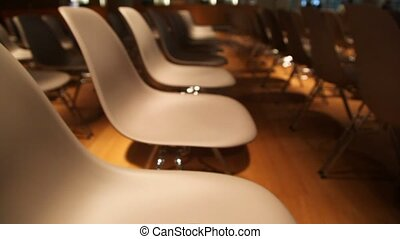 View moves from many to one chair with communicator on top in conference hall