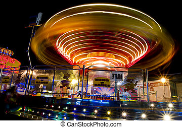 View of a amusement park ride in motion at night.