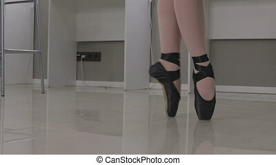 View of a ballerina standing en pointe on the tips of her...