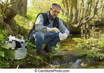 View of a Biologist take a sample in a river. - Scientist...