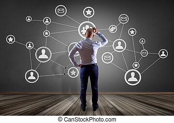 Businessman in front of a wall with a business network connection - business concept