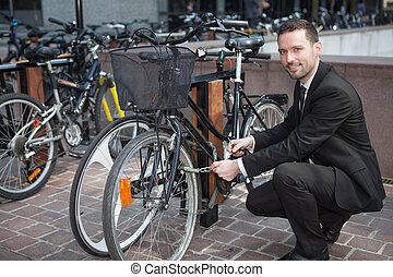 Businessman unlock his bike after a day of work