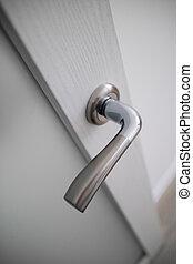 View of a door handle of an opened white door