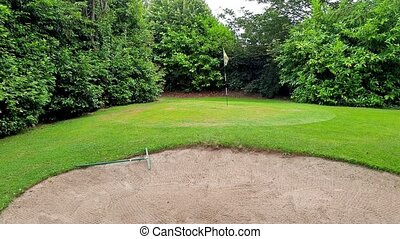 View of a golf course - hole with a flag pole and grass.