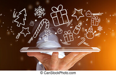 Hand of a man holding tablet with christmas icons all around