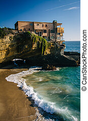 View of a house on a cliff and a small cove at Table Rock Beach, in Laguna Beach, California.