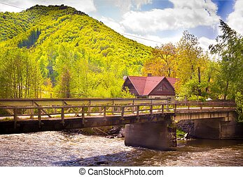 View of a house on bridge in Transylvania with river and mountain in background