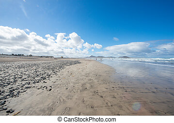 View of a large beach with a cloudy blue sky.