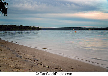 View of a large river with a sandy Bank against cloudy sky in the evening