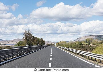 lonely road in a rural landscape - view of a lonely road in...