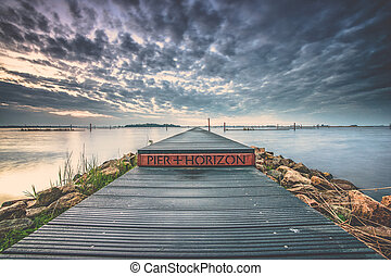 View of a long pier in the water with an infinite horizon