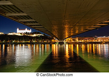 View of a medieval castle in Bratislava from under the bridge through Danube