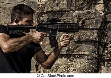 View of a menacing man pointing a machine gun in a black shirt and dark shades on a stone quarry.