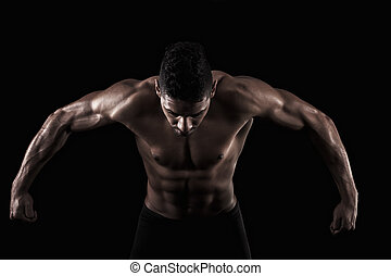muscled man on a black background - View of a muscled man on...