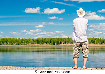 view of a piny pine young man with bare feet stands on a wooden pirsen against a beautiful lake