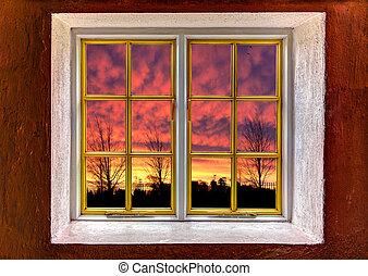 View of a purple orange sunset through a window