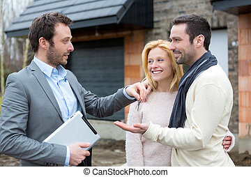 Real estate agent delivers keys to young atractive couple -...