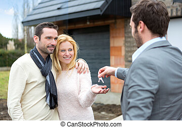 Real estate agent delivers keys to young atractive couple