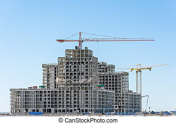 View of a residential complex under construction with high cranes. Large-scale building of the city