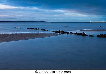View of a rocky coast in the evening. Long exposure shot.