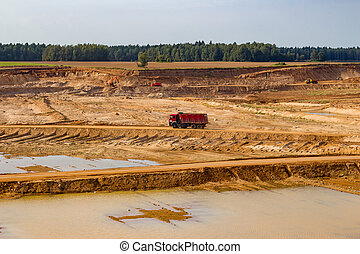 View of a sand pit and a moving red dump truck in the distance