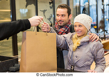 Seller giving bag to customers - View of a Seller giving bag...