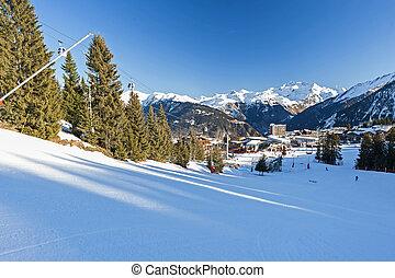 View of a ski piste in an alpine village ski resort
