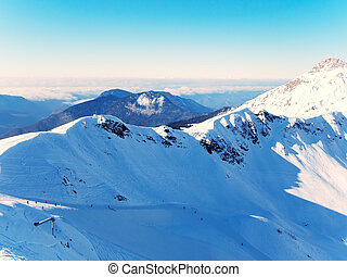 View of a snowy mountain valley with ski slopes against a blue sky. Photo from the top