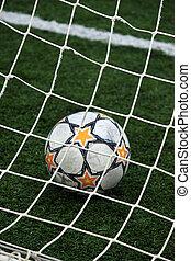 View of a soccer ball inside the goalpost