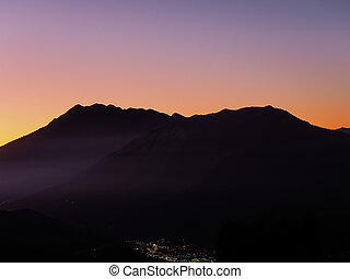 View of a town glowing in the distance surrounded by mountains against the sunset sky