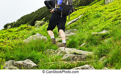 View of a trekker with a backpack walking up a hill