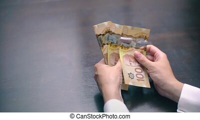View of a Woman Counting Many Canadian 100 Bills