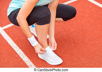 woman tie up her shoe laces at the stadium - View of a woman...