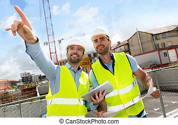 Worker and architect watching some details on a construction