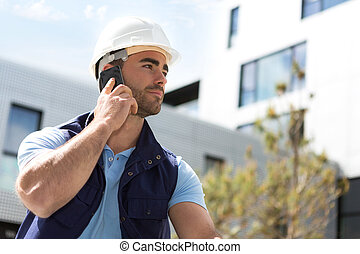 Yong attractive worker using mobile phone  on a construction site