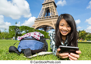 Young attractive asian tourist smartphone tablet in Paris