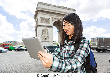 Young attractive asian tourist using tablet in Paris