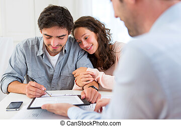 Young attractive couple signing contract