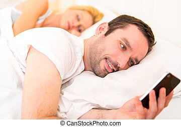 Young attractive man sending text in a bed - View of a Young...
