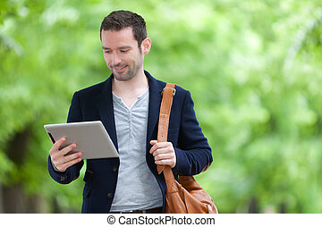 Young attractive man using tablet in Paris