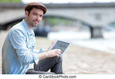 Young attractive tourist using tablet in Paris