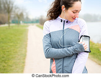 Young attractive woman adjust her music player before ...