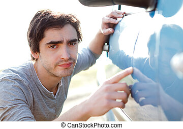 Young man looking for scratches on his car